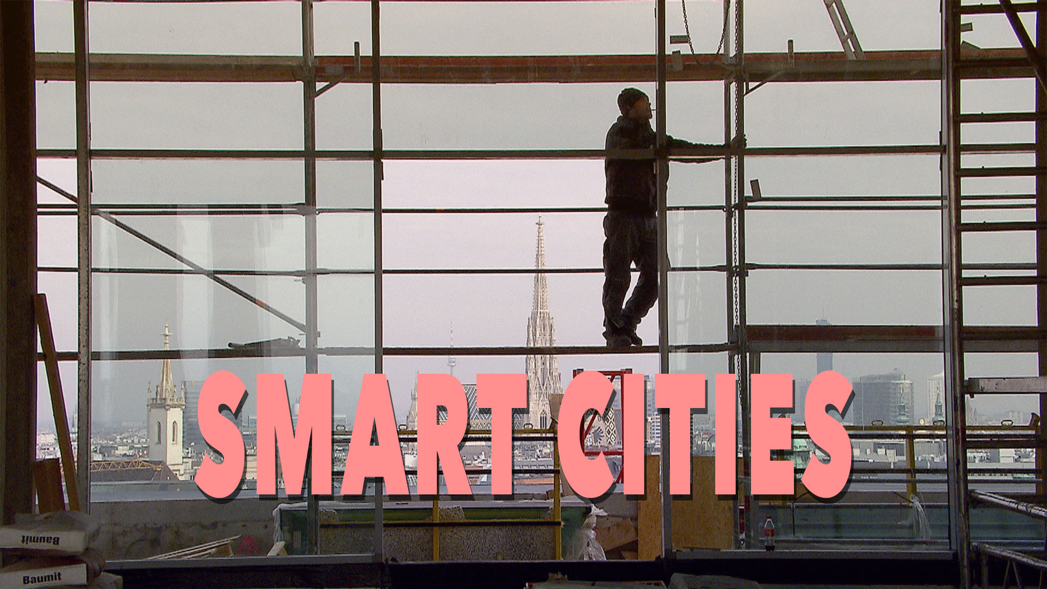 photo of a worker standing on scaffolding with a city scape view behind him acts as a link to Smart Cities film page