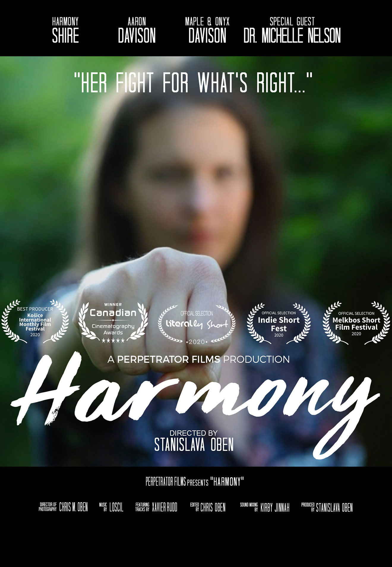 """poster photo of a closed fist of a woman facing us in the foreground, face of the woman blurry in the background acts as a link to the film page """"Harmony"""" on The Green Channel."""